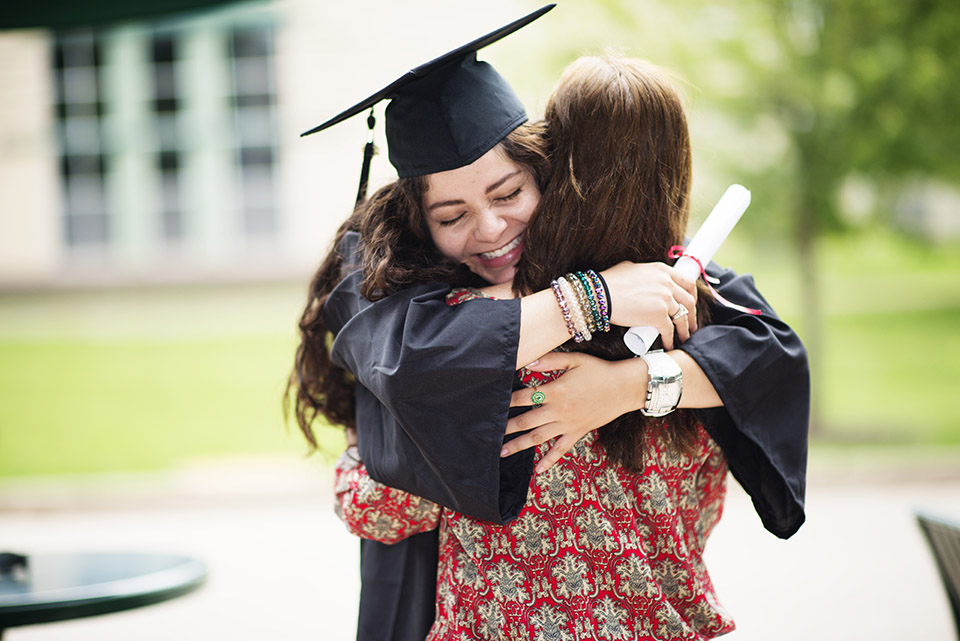 Foster mom hugging her foster daughter at graduation